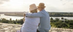 Man and woman sit on a hilltop looking out over a river both wearing invisible hearing aids.