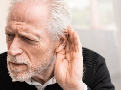 Senior man with his hand behind his ear because he is experiencing hearing loss symptoms. A recommendation for him would be to take the best free online hearing test on the Lexie Hearing website to determine his degree of hearing loss.