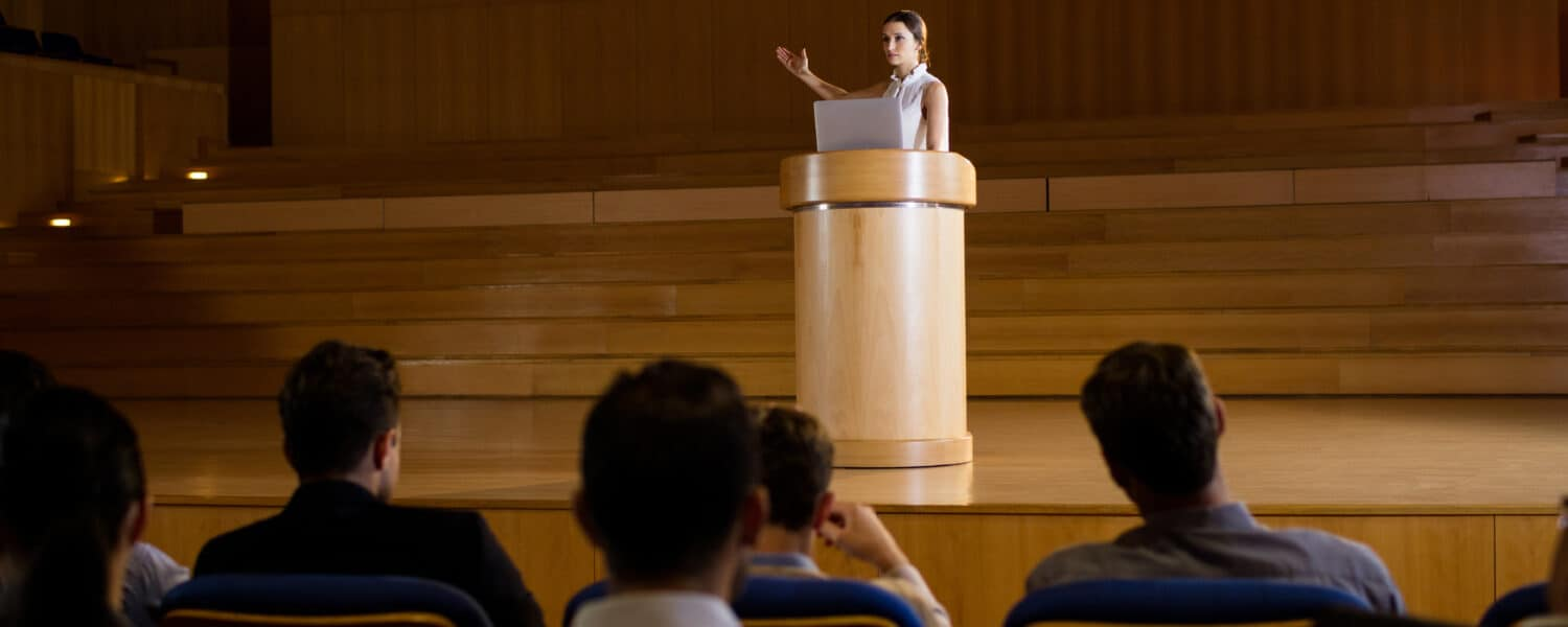what is a telecoil in a hearing aid? Female giving a speech in an auditorium with telecoils connecting to the audience's invisible hearing aids