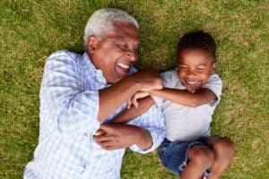 Grandfather with a best value hearing aid (a Lexie Lumen hearing aid) plays with his grandson on the grass