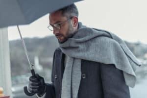Man walks with umbrella in rain wearing the best online hearing aids, Lexie Lumen hearing aids.