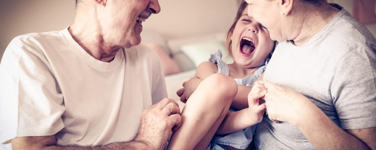 Grandmother and grandfather with hearing loss play with their granddaughter and after getting a hearing aid at an affordable price can hear their granddaughter laugh again..