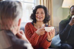 Middle aged woman meeting friends around table, wearing her best online hearing aid.