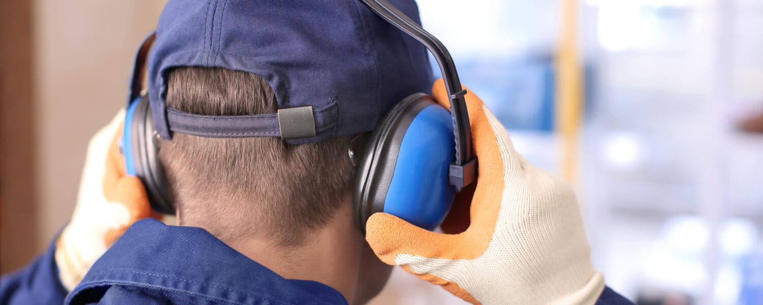 Man wearing hearing protectors to protect his ears in the workplace to prevent possibly having to see a hearing aid specialist due to a hearing loss.