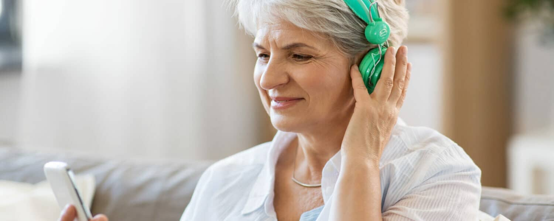 Senior woman wearing green headphones takes a free online hearing test.