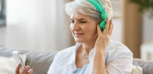 Senior woman wearing green headphones takes a free online hearing test.