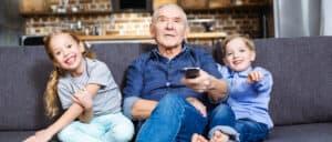 Man wearing best value hearing aids (Lexie Lumen hearing aids) with a hearing aid companion microphone watches television with grandchildren