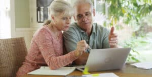 Senior couple using laptop to take the free online hearing test while wearing best value Lexie Lumen hearing aids.