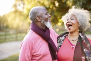 Senior couple walk in the countryside together. Woman is wearing a quality hearing aid.