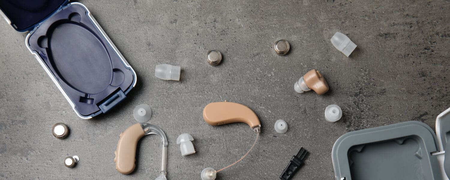 Flat lay composition with hearing aids and accessories on grey background, showcasing a quality hearing aid.