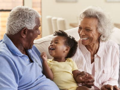 Grandfather, wearing invisible hearing aids, sits with granddaughter and the grandmother.