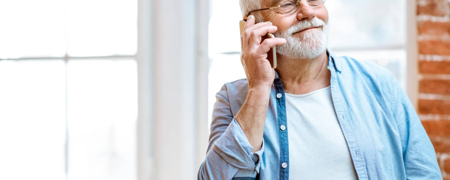 Senior man talks on the phone with a hearing aid specialist while wearing quality hearing aids