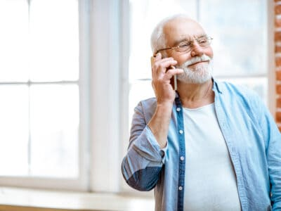 Senior man talks on the phone while wearing hearing aids
