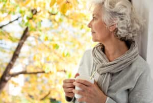 Woman with hearing loss looks out of window, holding a cup of coffee and thinking about taking a free online hearing test on the Lexie Hearing website.