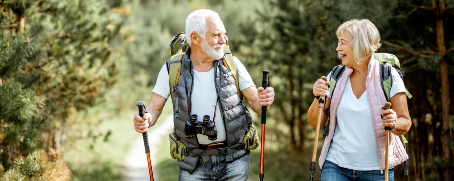 Happy senior couple wearing best value hearing aids hiking.