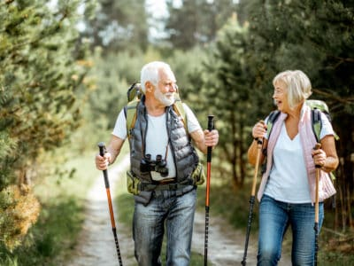 Happy senior couple wearing hearing aids hiking with trekking sticks and backpacks at the young pine forest
