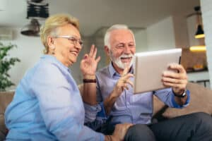 Smiling senior couple talk using visual cues on a video call with a hearing aid expert after taking the best online hearing test on the Lexie hearing website.