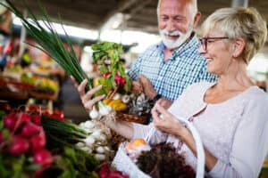 Mature couple shopping for groceries together both wearing invisible hearing aids.