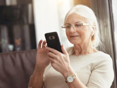 Senior woman wearing invisible hearing aids sits on the couch with her smartphone in her hand to consult a hearing aid expert online through the Lexie Hearing website.