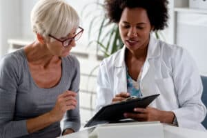 A female health practitioner and hearing aid expert sits at a table with a patient to discuss hearing loss, the best free online hearing test and a hearing aid price.