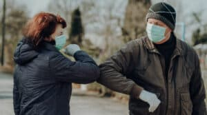 Two people wear face masks and premium hearing aids during the COVID-19 pandemic.