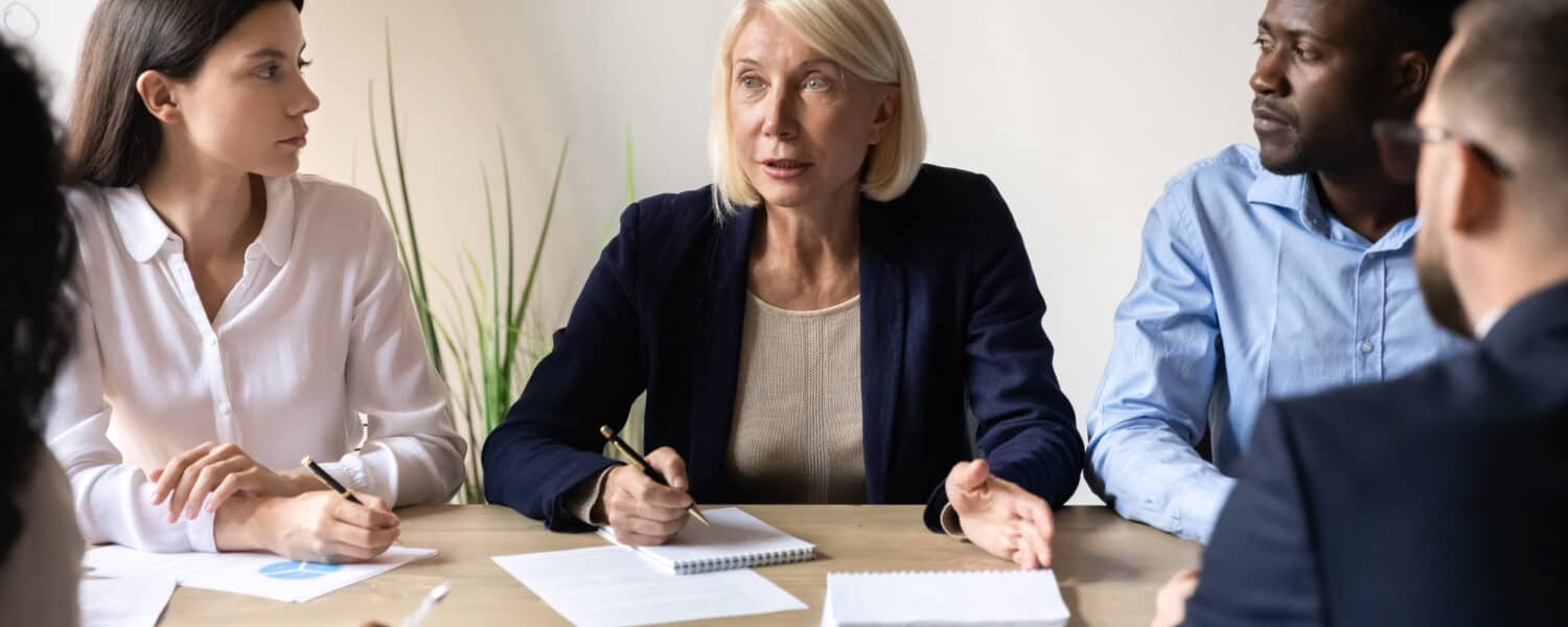 Middle aged businesswoman wearing quality hearing aids speaking to her team in a meeting.