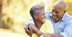 Senior couple embracing and smiling, man wears the best hearing aid available on the Lexie hearing website.