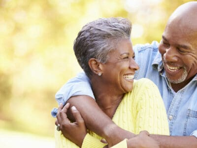 Senior couple embracing and smiling, man wears hearing aids.