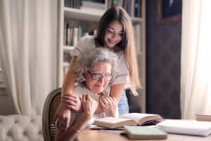 Grandmother wearing the best hearing aid (Lexie Lumen hearing aids) reads about how to improve her hearing loss