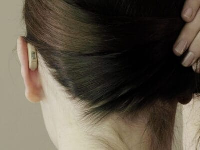 Woman wearing a very small, behind-the-ear Lexie hearing aid - the best hearing aid.