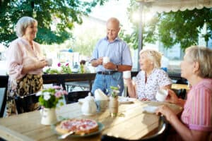Seniors at a restaurant discussing affordable hearing aid and hearing aid cost.