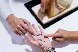 Hearing healthcare practitioner and hearing aid expert points to a premium and affordable hearing aid in a patient's hand.