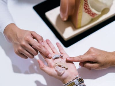 Hearing healthcare practitioner points to an expensive and affordable hearing aid in a patient's hand.