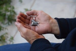 Very small and invisible Lexie Lumen hearing aids in palm of man's hands.
