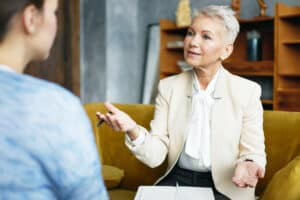 Middle-aged woman talks facing another identifiable woman. She uses hand gestures and other visual cues, as to accomodate the other woman that has a hearing loss and is wearing invisible hearing aids. tips to help with lipreading