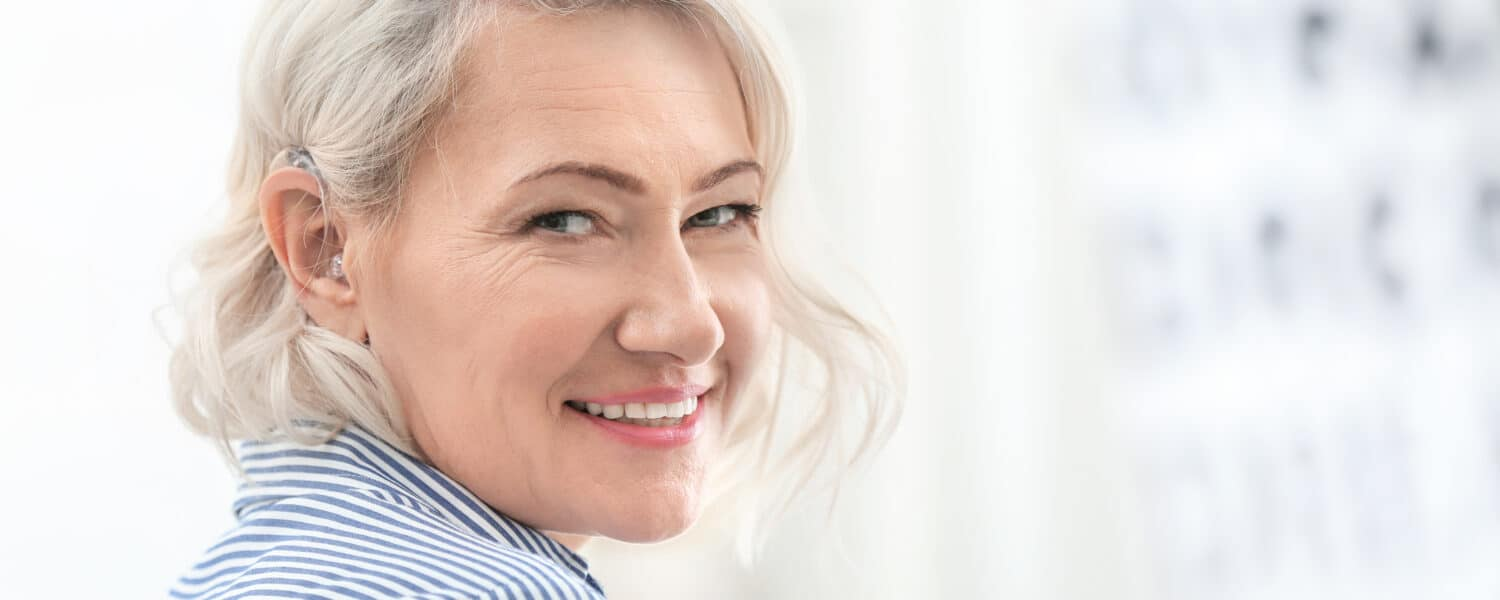 Middle-aged woman wearing invisible hearing aids looks over her shoulder, smiling as she bought the hearing aid at an affordable price.
