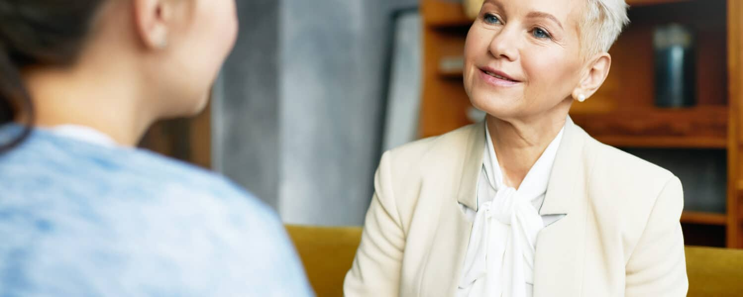 Middle-aged woman talks to another woman, practising to become a better listener after receiving her Lexie Lumen hearing aid at an affordable price.