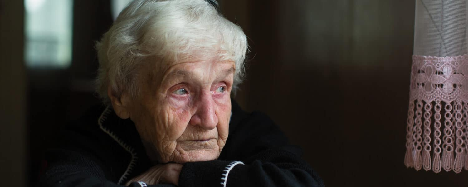 Depressed older woman looks out of the window sadly as she is in serious need of a premium hearing aid