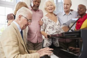 A group of 5 senior friends stand around the piano, playing and singing together after all of them took the most accurate online hearing test on the Lexie Hearing website to show the correlation between hearing loss and music