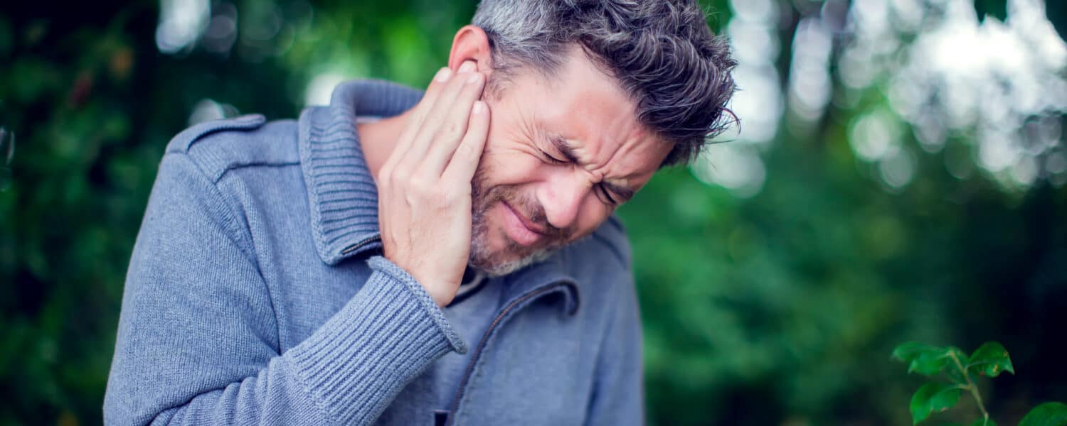 Middle-aged man with tinnitus standing in a garden. He is in pain and considering getting a hearing aid at an affordable price to help with his tinnitus symptoms