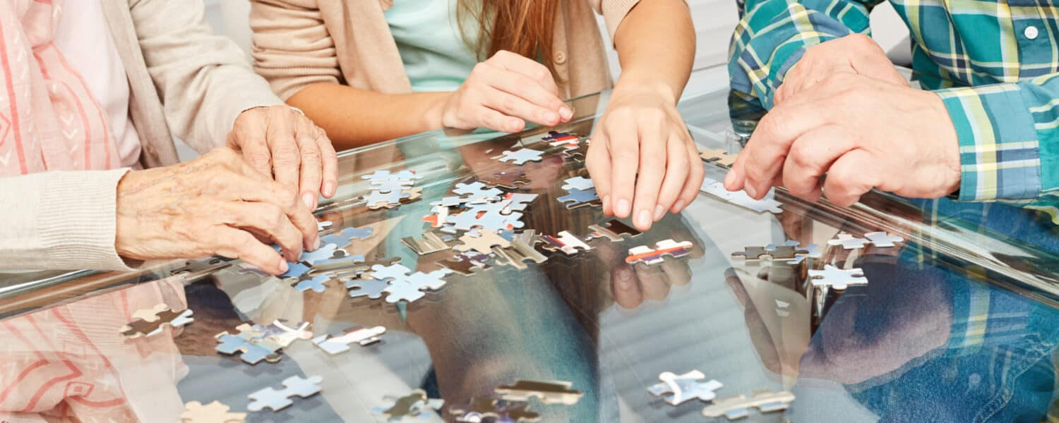 Three people sit around a table building a puzzle together waiting for their best value hearing aid to be delivered. The puzzle shows the elderly woman is working on her hearing loss and memory.