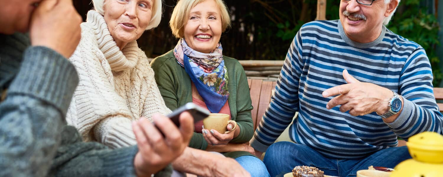 A group of four senior sit together, talking loudly, smiling and discussing hearing aid cost