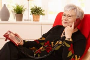 Senior woman sits on red chair talking on a landline telephone after she hears the phone ring through her best value hearing aid
