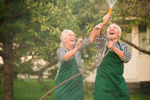 Elderly couple outside playing with the sprayer and learning how to get moisture out of hearing aids