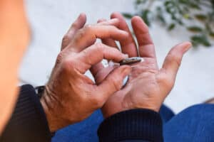 Two male hands hold two small, gray Lexie Lumen quality hearing aids after taking a fast online hearing test