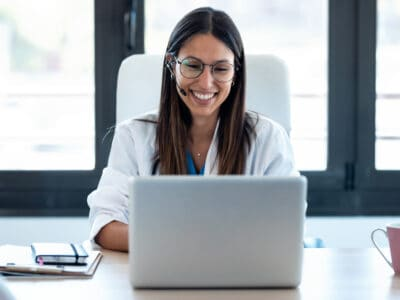 A smiling, female hearing aid professional consults with a customer via a video call after customer took the best free online hearing test