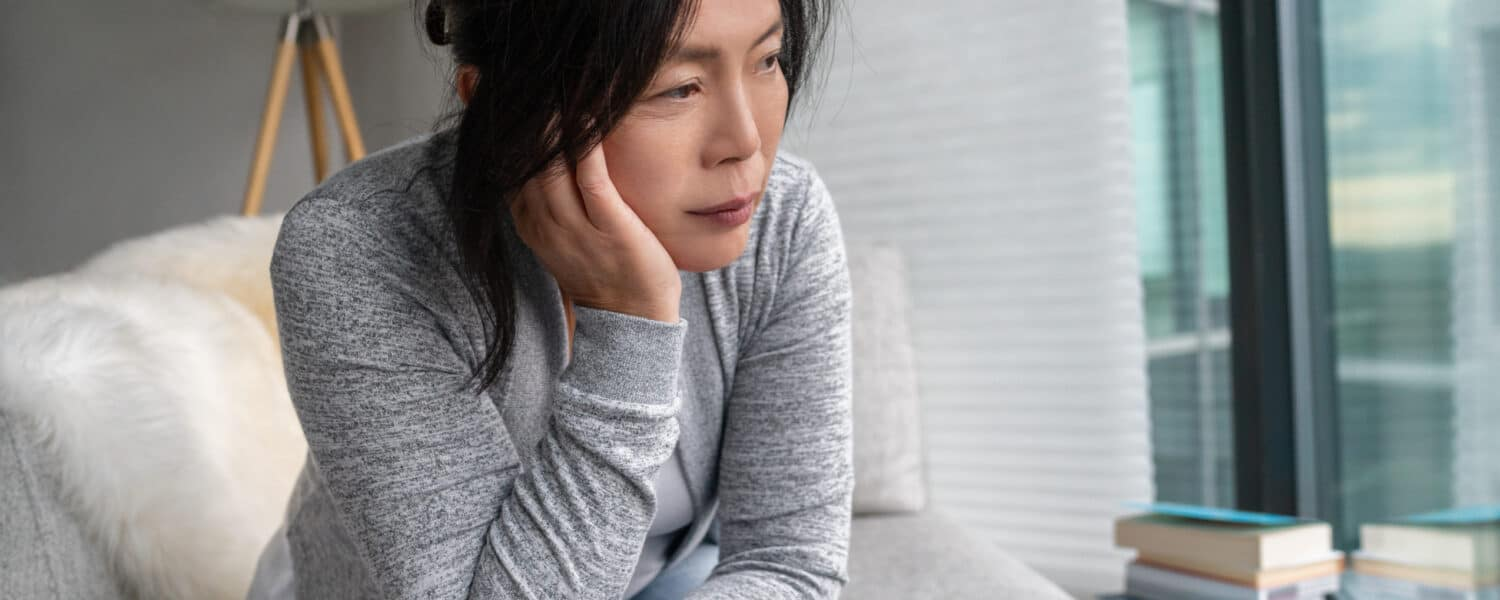 Woman wearing a hearing aid sits on the couch looking frustrated and about to call a hearing aid specialist for assistence with her premium hearing aid