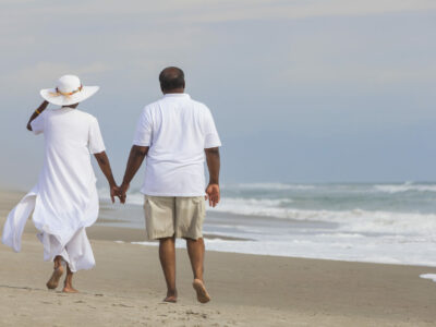 African American couple walking along the seashore holding hands and discussing wearing Lexie Lumen hearing aids in windy conditions