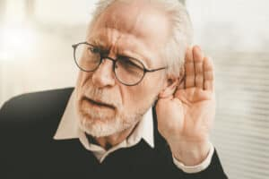 Elderly man with his hand behind is hear to hear better indicating he has a hearing loss.