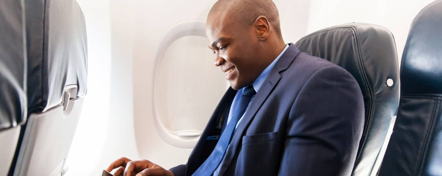 Man sitting on on airplane with his smartphone in his hand wearing invisible hearing aids to asssisting him with traveling with a hearing loss